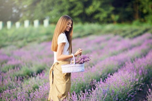 Uśmiechnięta kobieta spacerująca z koszem lawendowym polem