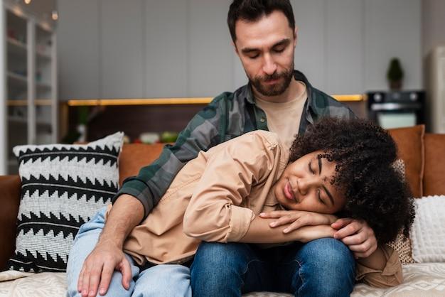 Uśmiechnięta kobieta śpi na nogach chłopaka