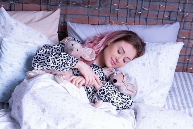 Uśmiechnięta kobieta śpi w łóżku ze swoimi myszami tilda