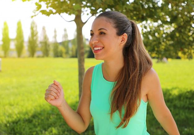 Uśmiechnięta kobieta sportowy na świeżym powietrzu w parku.