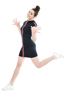 Uśmiechnięta kobieta sportowy skoki na białym tle na białym tle. patrząc na aparat