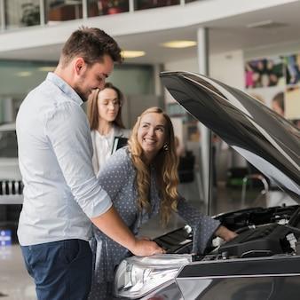 Uśmiechnięta kobieta sprawdza samochodowego silnika