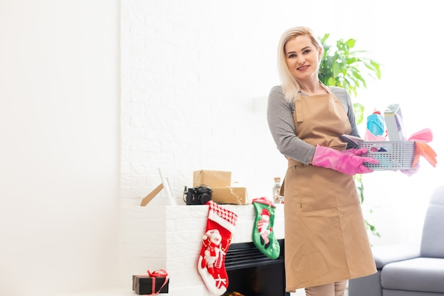 Uśmiechnięta kobieta sprzątająca dom przed bożym narodzeniem