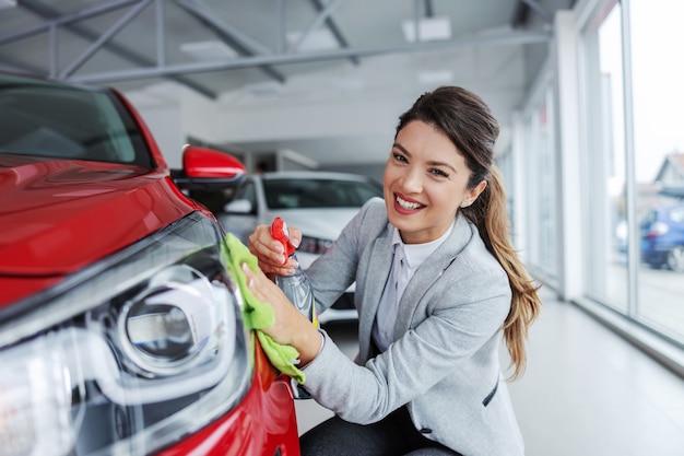 Uśmiechnięta kobieta sprzedawca samochodów w garniturze skulona i wycierająca samochód detergentem. wnętrze salonu samochodowego.
