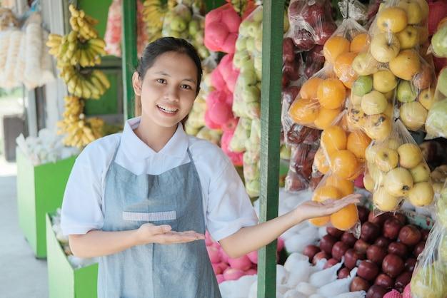 Uśmiechnięta kobieta sprzedawca stoi w pobliżu wyświetlacza świeżych owoców na rynku owoców