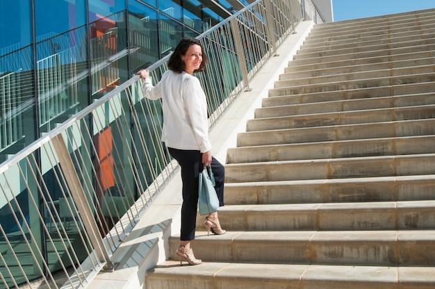 Uśmiechnięta kobieta stoi przy schodach, obracając głowę z powrotem do kamery