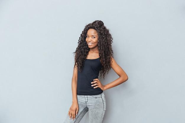 Uśmiechnięta kobieta stojąca na szarej ścianie i patrząca na przód