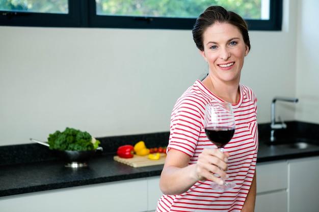 Uśmiechnięta kobieta stojąca w kuchni trzyma kieliszek wina