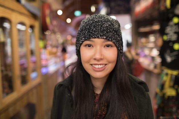 Uśmiechnięta kobieta stojąca w supermarkecie