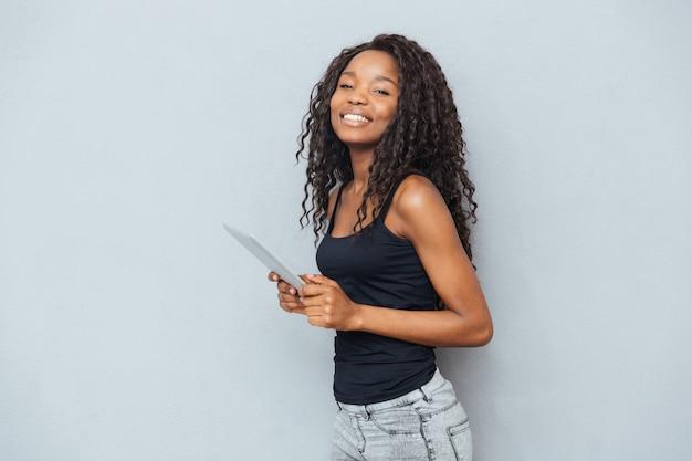 Uśmiechnięta kobieta stojąca z komputerem typu tablet nad szarą ścianą i patrząca na przód