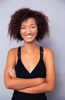 Uśmiechnięta kobieta stojąca z rękoma na szarej ścianie