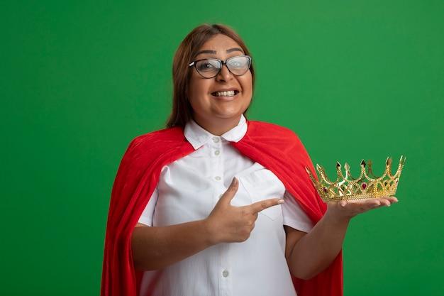 Uśmiechnięta kobieta superbohatera w średnim wieku w okularach trzyma i wskazuje na koronę odizolowaną na zielono