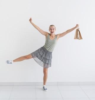 Uśmiechnięta kobieta tańcząca z ekologicznymi torbami na zakupy i kartą kredytową
