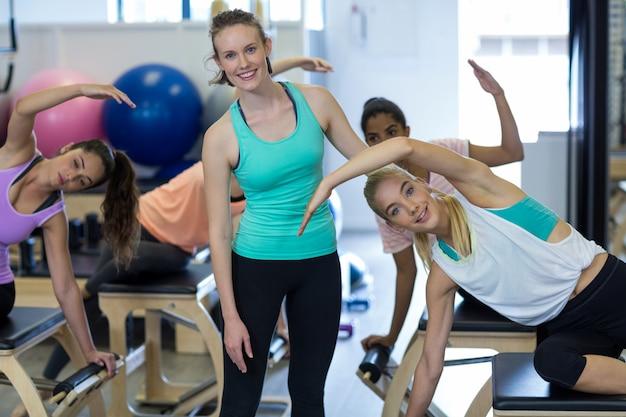 Uśmiechnięta kobieta trener pomaga kobiecie z ćwiczeniami