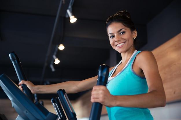 Uśmiechnięta kobieta treningu na maszynie ćwiczeń w siłowni fitness i patrząc na przód