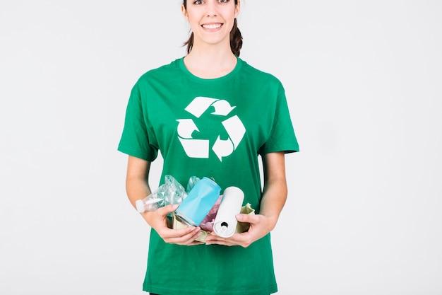 Uśmiechnięta kobieta trzyma blaszane puszki i plastikowe butelki