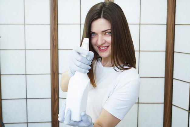 Uśmiechnięta kobieta trzyma butelkę z rozpylaczem z środkiem antyseptycznym lub detergentem, jak pistolety