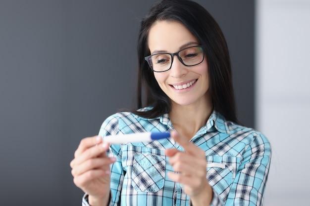 Uśmiechnięta kobieta trzyma ciąży test zbliżenie
