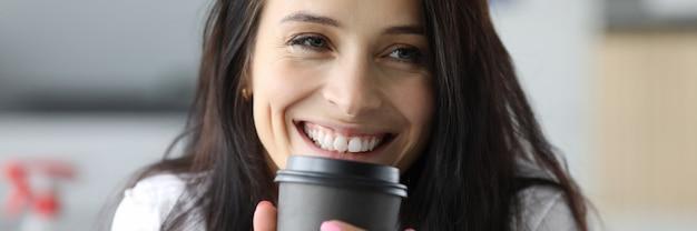 Uśmiechnięta kobieta trzyma czarnego papierowego kubek