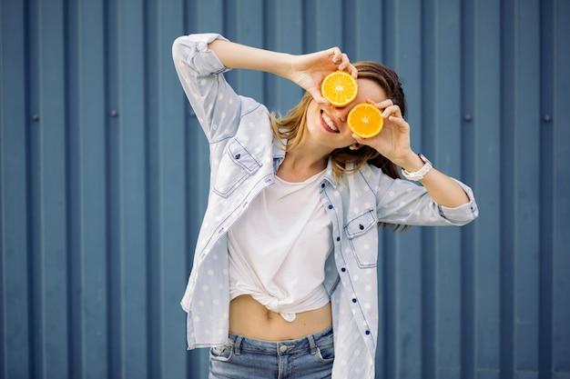 Uśmiechnięta kobieta trzyma dwa pomarańcze w rękach