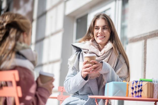Uśmiechnięta kobieta trzyma filiżankę kawy, siedząc w kawiarni na świeżym powietrzu z teen girl