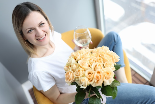 Uśmiechnięta kobieta trzyma kieliszek wina i bukiet kwiatów w dłoniach