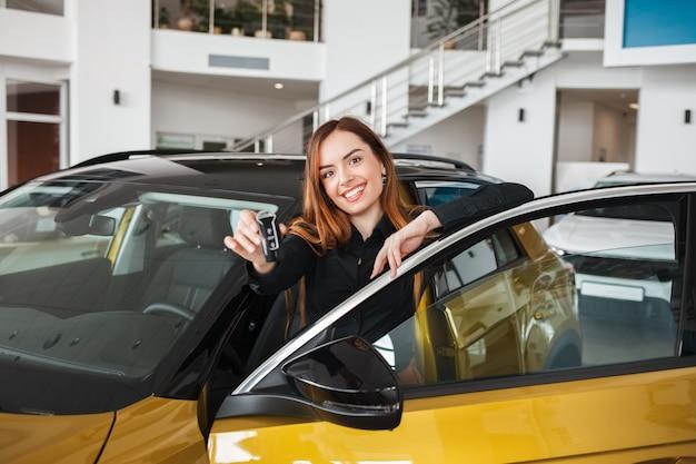 Uśmiechnięta kobieta trzyma klucz do samochodu