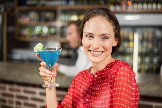 Uśmiechnięta kobieta trzyma koktajl