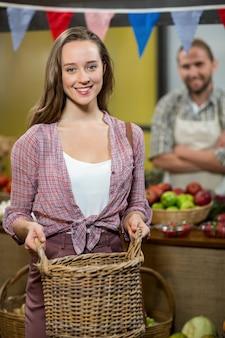 Uśmiechnięta kobieta trzyma kosz przy kasie w sklepie spożywczym
