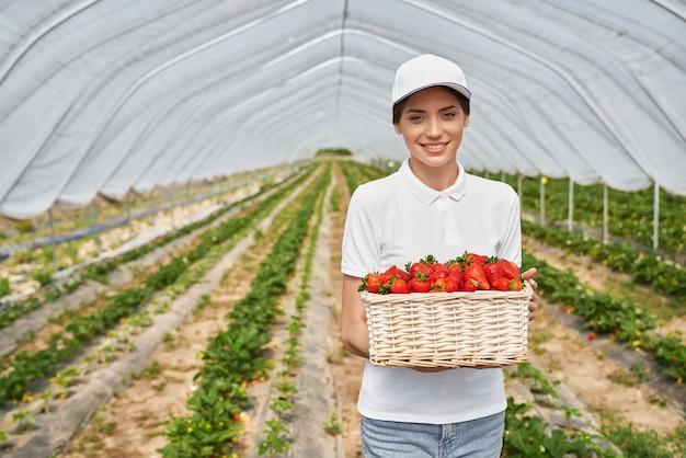 Uśmiechnięta kobieta trzyma kosz z czerwonymi dojrzałymi truskawkami