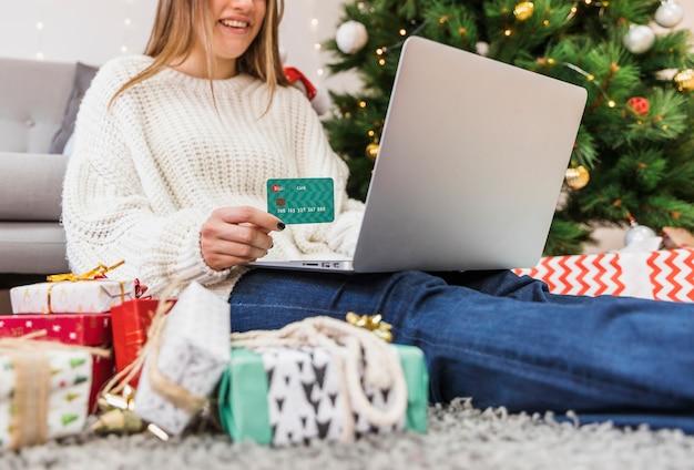Uśmiechnięta kobieta trzyma kredytową kartę i laptop