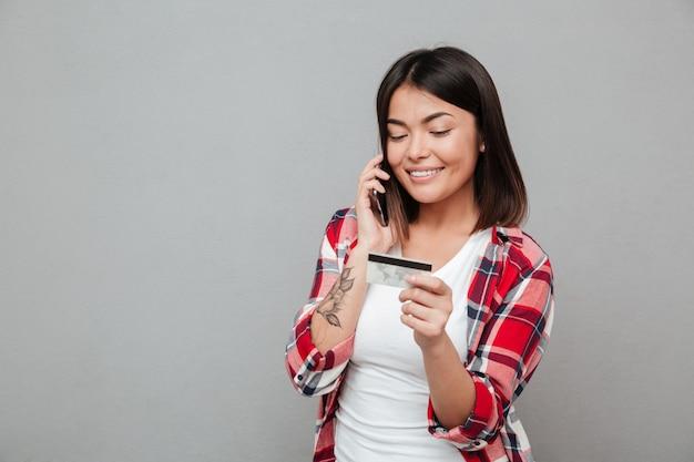 Uśmiechnięta kobieta trzyma kredytową kartę i opowiada telefonem komórkowym