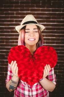 Uśmiechnięta kobieta trzyma kształt serca