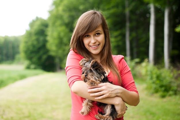 Uśmiechnięta kobieta trzyma ładny szczeniak