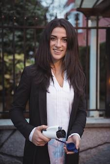 Uśmiechnięta kobieta trzyma ładowarkę samochodową na stacji ładowania pojazdów elektrycznych