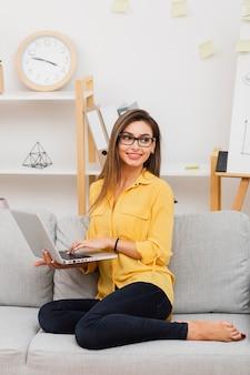 Uśmiechnięta kobieta trzyma laptop i patrzeje daleko od