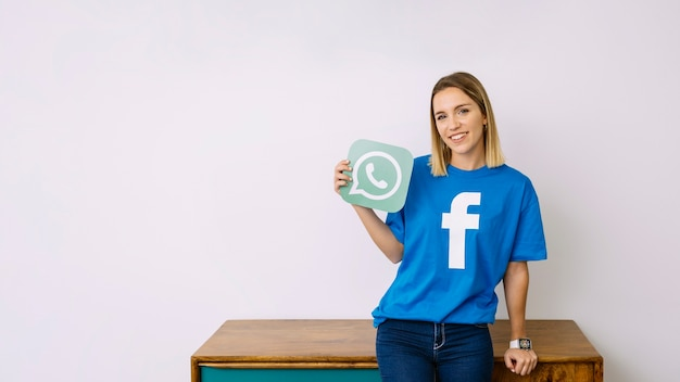 Uśmiechnięta kobieta trzyma logo whatsup