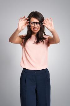 Uśmiechnięta kobieta trzyma okulary mody