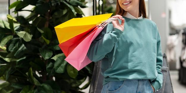 Uśmiechnięta kobieta trzyma papierowe torby