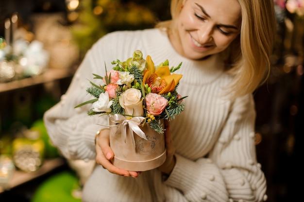 Uśmiechnięta kobieta trzyma pudełko koloru brzoskwini z różowymi różami i żółtą orchideą