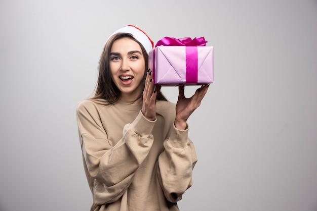 Uśmiechnięta kobieta trzyma pudełko prezentów bożonarodzeniowych.