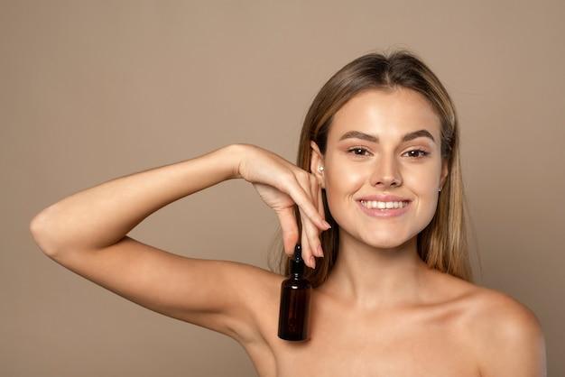 Uśmiechnięta kobieta trzyma serum witaminy c w pobliżu jej twarzy na beżowym tle. koncepcja pielęgnacji skóry i zdrowia.