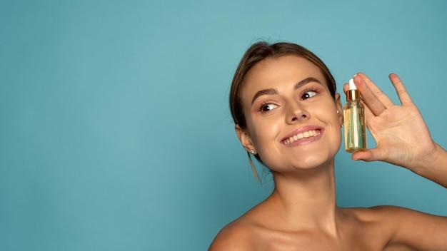 Uśmiechnięta kobieta trzyma serum witaminy c w pobliżu jej twarzy na niebieskim tle. koncepcja pielęgnacji skóry i zdrowia. baner internetowy.