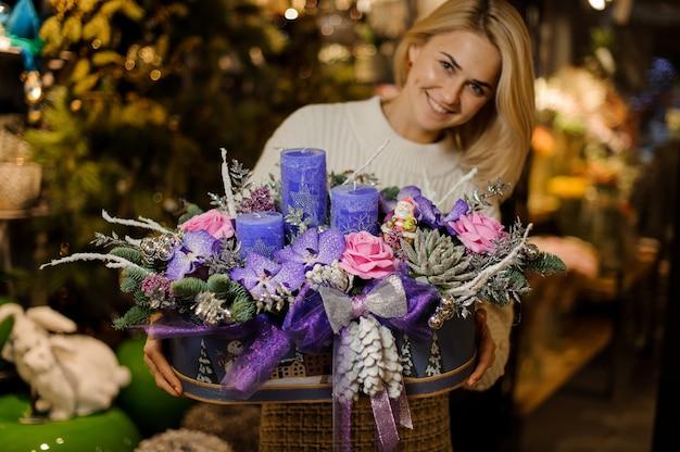 Uśmiechnięta kobieta trzyma świąteczną kompozycję z fioletowymi i różowymi kwiatami, sukulentami, jodłą i świecami