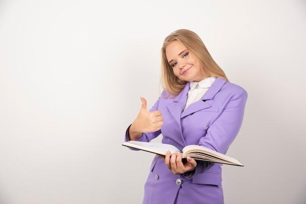 Uśmiechnięta kobieta trzyma tabletkę na białym.