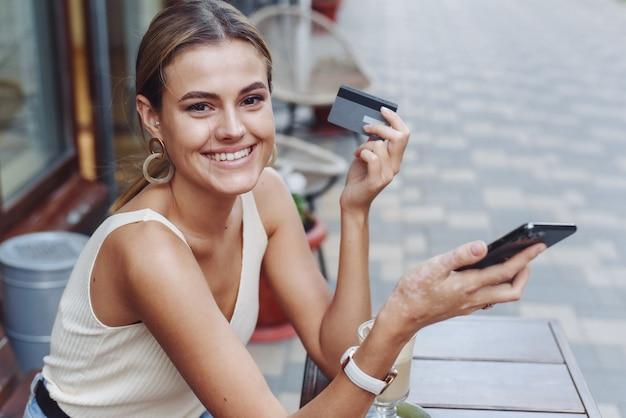 Uśmiechnięta kobieta trzyma telefon i kartę kredytową na zewnątrz w kawiarni.