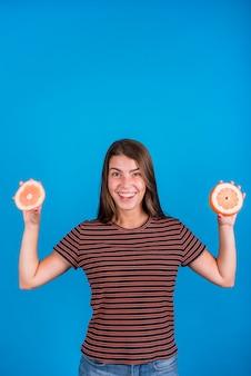 Uśmiechnięta kobieta trzyma tnące części na grapefruitowym