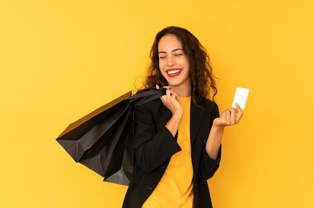 Uśmiechnięta kobieta trzyma torby i płaci za zakup kartą kredytową