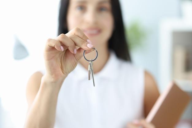 Uśmiechnięta kobieta trzyma w dłoni klucze do mieszkania