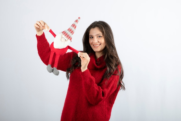 Uśmiechnięta kobieta trzyma zabawkę świętego mikołaja w jej ręce. .